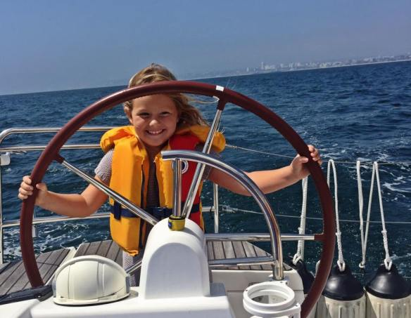 Athena manning the helm on Mojo sailboat